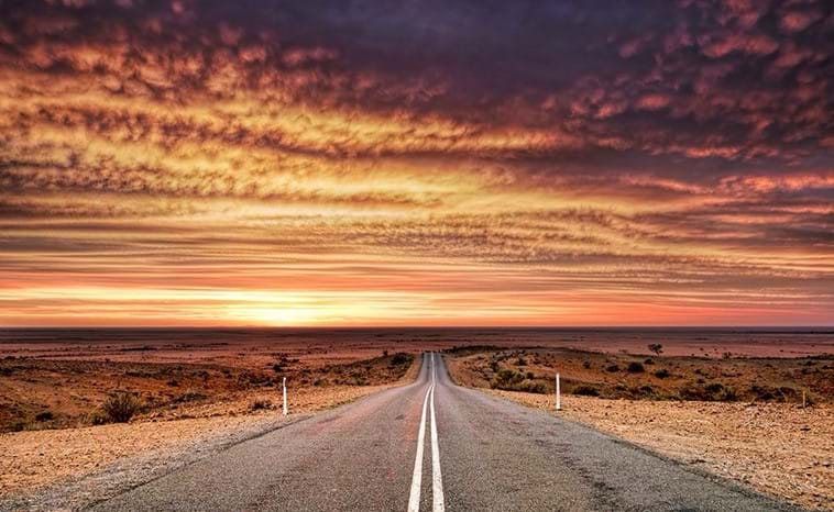 An deserted outback road scene at sunset
